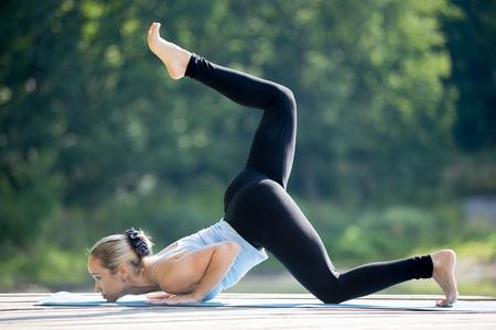 yoga outside: Beautiful sporty fit blond young woman in sportswear working out outdoors in park on summer day, doing variation of Caterpillar posture, Eka Pada Ashtanga Namaskarasana, Eka Pada Ganda Bherundasana