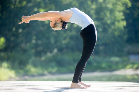 ardha: Beautiful sporty fit blond young woman in blue tank top sportswear working out outdoors on summer day, doing Standing Backward Bend yoga posture, Ardha Chakrasana, full length