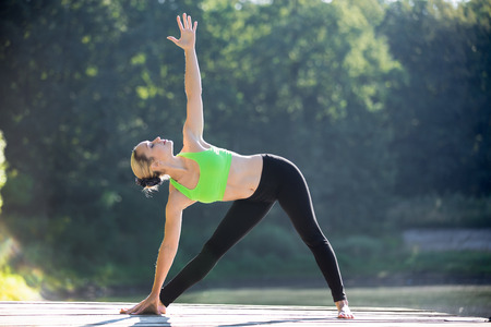 Beautiful sporty fit blond young woman in green sportswear working out outdoors on wooden deck, standing in Utthita Trikonasana, Extended Triangle posture, full length