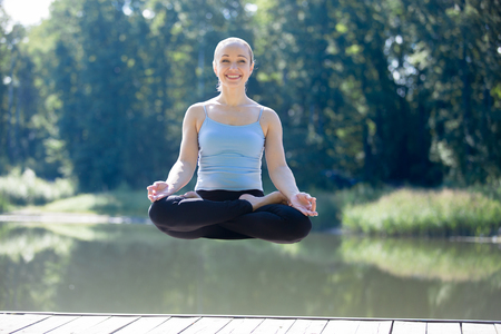 levitating: Portrait of happy smiling young beautiful woman meditating in midair, floating outdoors above ground, working out in park on summer day, sitting with crossed legs in Lotus Posture, Padmasana Stock Photo