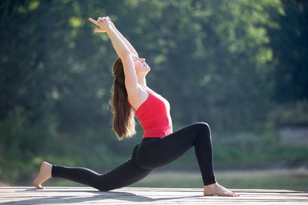 estiramiento: Ajuste a la mujer joven que trabaja al aire libre en el parque el día de verano, que hace estocada de media luna pose (anjaneyasana), la postura del caballo (Ashva sanchalasana), que se extiende flexores de la cadera y cuádriceps