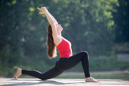 quadriceps: Fit young woman working out outdoors in park on summer day, doing crescent lunge pose (anjaneyasana), Horse posture (ashva sanchalasana), stretching hip flexors and quadriceps Stock Photo