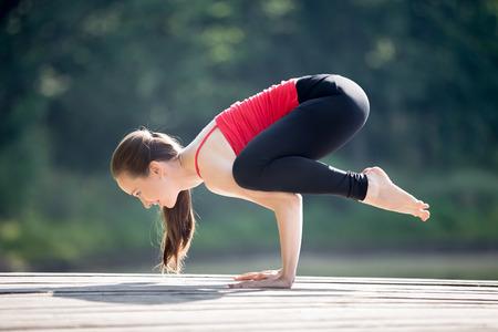 cuervo: Ajuste a la mujer joven hermosa sonriente vistiendo camiseta roja y leggings negros deportivo ejercicio al aire libre en el parque el d�a de verano, haciendo Crane (Crow) Pose, Bakasana (Kakasana), de cuerpo entero