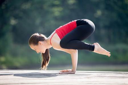 Fit young beautiful smiling woman wearing red tank top and black sporty leggings working out outdoors in park on summer day, doing Crane (Crow) Pose, Bakasana (Kakasana), full length Reklamní fotografie