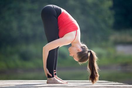 フィット若い美しい女性赤のタンクトップと黒のスポーティなレギンス夏の日、公園で屋外作業を身に着けている Uttanasana 膝姿勢に立って頭をやっ