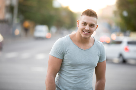good looking guy: Young happy smiling good looking guy wearing casual clothing walking on the evening street with transport traffic on the background