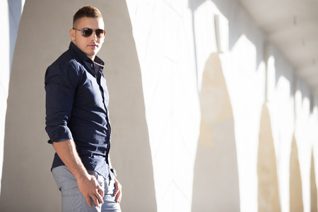 passageways: Portrait of young handsome man wearing blue shirt and sun glasses standing on the street beside white stucco wall with arched passageways, posing, copy space