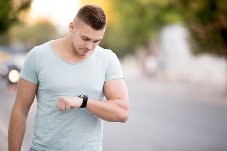 Confident good looking young guy looking at his watch on the street, young man wearing casual clothing checking time