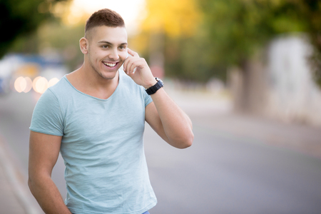 phonecall: Portrait of happy smiling good looking young guy wearing casual clothing walking on the street, holding mobile phone, using smartphone, talking on the phone, copy space Stock Photo
