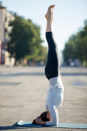 supported: Yoga in the city: beautiful young sporty woman working out on the road on summer day, doing supported headstand posture, salamba sirshasana, full length, profile view