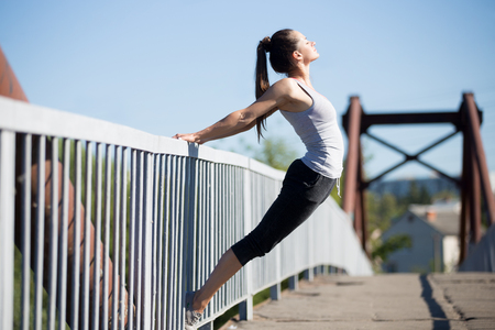 respiracion: Yoga en la ciudad: adolescente hermoso deportivo que se resuelve en el puente viejo en día de verano, haciendo salto mortal hacia atrás en la barandilla, calentar los músculos, respirar aire fresco Foto de archivo