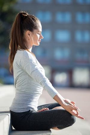 respiracion: Yoga en la ciudad: hermosa mujer joven que llevaba meditando en forma de ropa deportiva, la respiración, sentado con las piernas cruzadas en el Medio Loto Postura en la calle en día de verano, Ardha Padmasana, de cuerpo entero