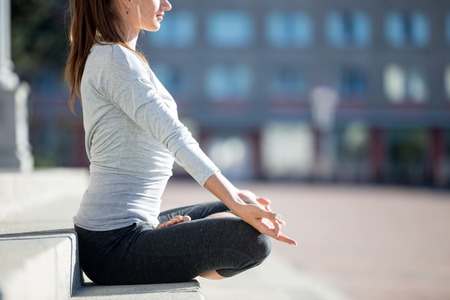 siddhasana: Yoga in the city: beautiful young fit woman wearing sportswear meditating on the street on summer day, sitting with crossed legs in Half Lotus Posture, Ardha Padmasana, close up