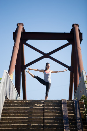 big toe: Yoga in the city: beautiful young fit woman working out on the old bridge on summer day, doing Utthita Hasta Padangustasana, Extended Hand to Big Toe posture, full length Stock Photo