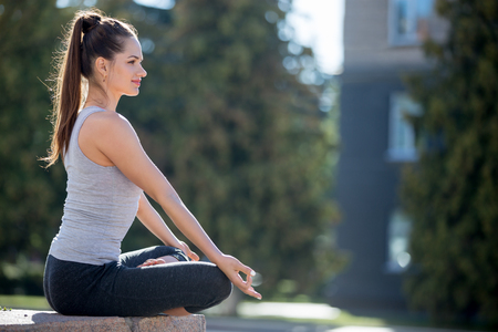 Yoga in the city: beautiful young fit woman wearing sportswear meditating, breathing, sitting with crossed legs in Half Lotus Posture on the street on summer day, Ardha Padmasana, copy space Stock Photo