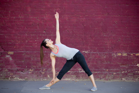 simple girl: Yoga in the city: smiling beautiful sporty young woman working out on summer day on the street in front of old red brick wall, doing Utthita Trikonasana, Extended Triangle posture