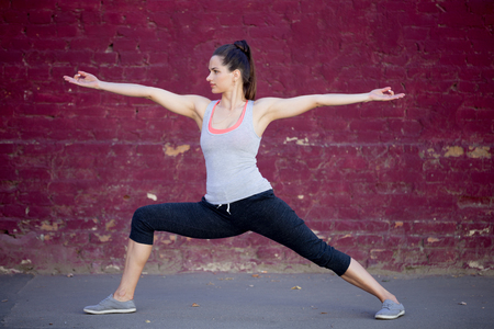 female warrior: Yoga in the city: beautiful sporty young woman working out on summer day on the street in front of old red brick wall, doing Warrior II posture (Virabhadrasana 2)