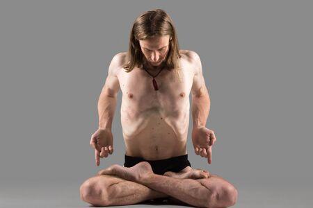 pranayama: Sporty muscular young yogi man sitting cross-legged in lotus posture, meditating, practicing pranayama techniques in padmasana, studio shot on dark background, full length