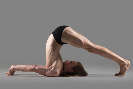 plough: Sporty muscular young yogi man doing halasana, plough pose (yin yoga snail posture), studio shot on dark grey background, side view, full length