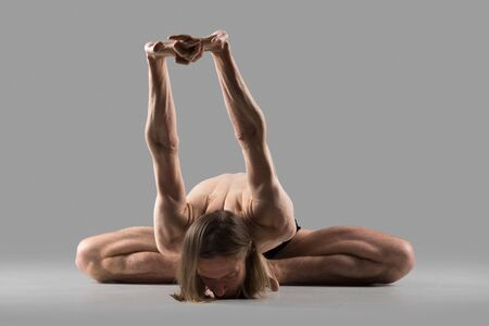 baddha: Sporty young man sitting in deep variation of baddha konasana posture (purna titli, bound angle, cobbler, butterfly pose) with arms stretched behind the back, studio full length shot Stock Photo