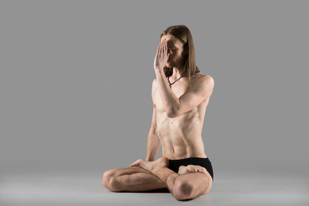 nostril: Sporty muscular young yogi man sitting cross-legged in lotus posture, padmasana, practicing Breathing technique Anuloma Viloma pranayama (alternate nostril breathing), studio shot on dark background