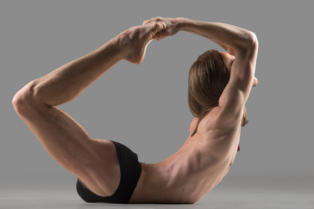 dhanurasana: Sporty muscular young yogi man doing backbend exercise, dhanurasana, Bow Posture, studio shot on dark background, side view, full length