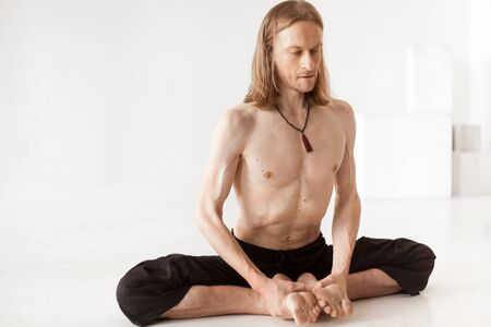 baddha: Sporty young man in black trousers sitting in baddha konasana posture (purna titli, bound angle, cobbler, butterfly pose), studio full length shot, three-quarters view