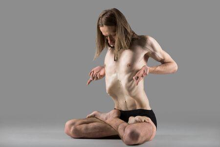 pranayama: Sporty muscular young yogi man sitting cross-legged in lotus posture, padmasana, practicing Upward Abdominal Lock, Uddiyana Bandha during pranayama, studio shot on dark background, full length