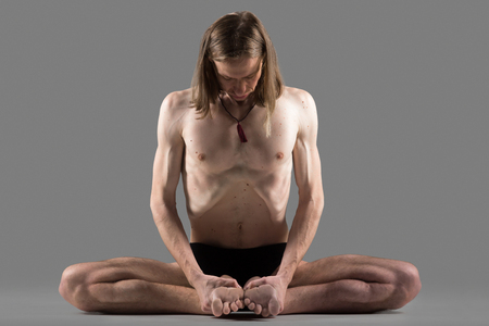 konasana: Sporty young man sitting in variation of goraksasana, baddha konasana posture (purna titli, bound angle, cobbler, butterfly pose), studio full length shot