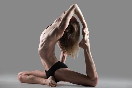 muscle training: Sportlich muskulösen jungen Yogi Mann tut Variation One Legged Königlichen Pigeon Pose 1, Eka Pada Rajakapotasana Ich Haltung, studio shot auf dunklem Hintergrund, Seitenansicht, in voller Länge