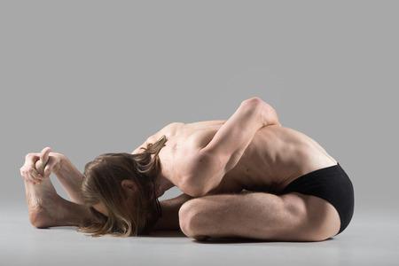 baddha: Sporty muscular young yogi man doing half bound lotus forward bend, ardha baddha padma paschimottanasana, Ardha Baddha Padmasana, studio shot on dark background, full length Stock Photo