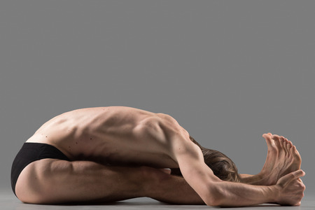 situp: Sporty muscular young yogi man sitting in paschimottanasana (Intense Dorsal Stretch) pose, seated forward bend posture, exercise for hips and spine, studio shot, side view, full length