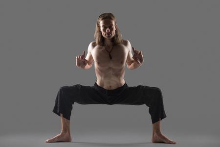 straddle: Sporty young man in black pants doing strengthening yoga pose, standing in rudrasana (sumo), utkata konasana (goddess or temple pose), Horse Stance, studio shot on gray background, full length Stock Photo