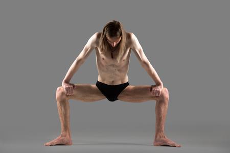 straddle: Sporty young yogi man doing strengthening yoga posture, standing in rudrasana (sumo), utkata konasana (goddess or temple pose), studio shot on gray background, full length, front view