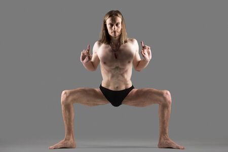 konasana: Sporty young yogi man standing in rudrasana (sumo), utkata konasana (goddess, fiery angle or temple pose), doing exercise for hips, groins and chest, studio shot on dark background, full length