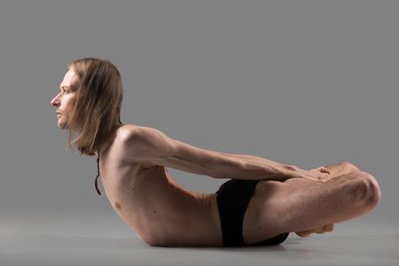 baddha: Sporty muscular young yogi man doing backbend exercise, Viparita Baddha Matsyasana, studio shot on dark background, side view, full length