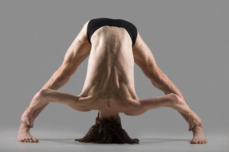 to bend: Sporty muscular young yogi man doing Wide-Legged Forward Bend, Prasarita Padottanasana posture (Dandayamana Bibhaktapada Paschimotthanasana), studio shot on dark background, full length