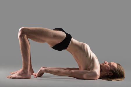 dwi: Sporty muscular young yogi man with long hair doing bridge posture, Setu Bandha Sarvangasana, studio shot on dark grey background, side view, full length