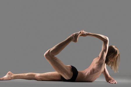 dhanurasana: Sporty muscular young yogi man doing backbend exercise, Ardha dhanurasana (Half Bow Pose), Eka Pada Padangustha Dhanurasana Posture, studio shot on dark background, side view, full length