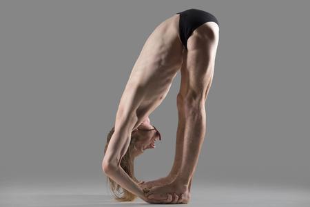 pada: Sporty muscular young yogi man doing Hands to Feet Pose, Padahastasana, variation of Uttanasana posture, asana for hamstrings, back, neck and shoulders, studio shot on dark background, full length
