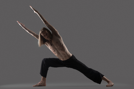 side angle pose: Sporty young man in black trousers doing lunge exercise, standing in strength variation of Extended Side Angle Pose, Utthita Parsvakonasana, studio shot on gray background, full length