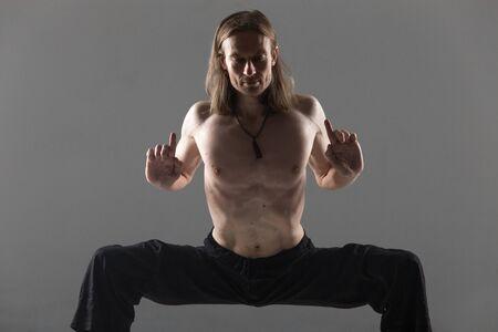 konasana: Portrait of sporty young man in black pants doing strengthening yoga pose, standing in rudrasana (sumo), utkata konasana (goddess or temple pose), studio shot on gray background, full length