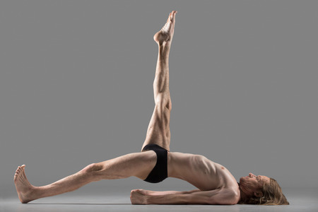 dwi: Sporty muscular young yogi man doing one-legged variation of bridge posture, Eka Pada Setu Bandha Sarvangasana, Utthita Eka Pada Pithasana, studio shot on dark background, side view, full length