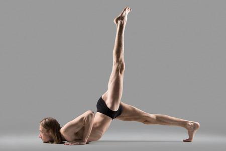 life extension: Sporty muscular young yogi man doing Eka Pada Salabhasana, one legged Locust Pose, or advanced variation of Eka Pada Ashtanga Namaskara, studio shot on dark background, side view, full length Stock Photo