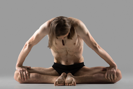 baddha: Sporty young man sitting in variation of baddha konasana posture (purna titli, bound angle, cobbler, butterfly pose), studio full length shot