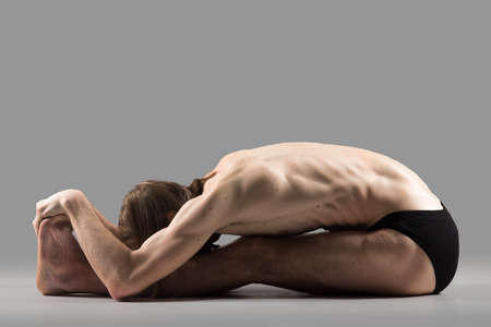 situp: Sporty muscular young yogi man doing sit-up, sitting in paschimottanasana pose, seated forward bend posture, studio shot on dark background, side view, full length