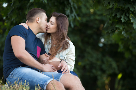 male and female: Portrait of beautiful young couple in love wearing casual clothes gently kissing in park, sitting together on grass on summer day, copyspace