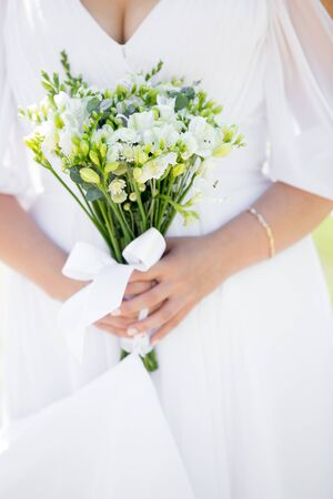 decollete: Young bride in dress with decollete holding in hands wedding bouquet made with white blossoms, close up, focus on flowers