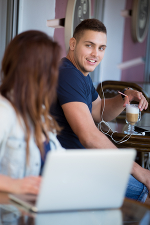 Handsome guy in casual clothes sitting in street cafe with a drink, flirting and looking with admiration at beautiful young woman with laptop at the next table