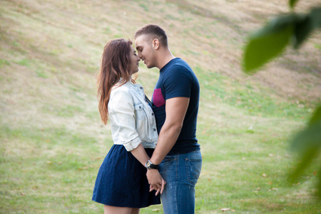 couple having fun: Happy smiling attractive young couple on a date standing close to each other in park, about to kiss, snuggling, touching faces, holding hands, flirting, talking, having fun together